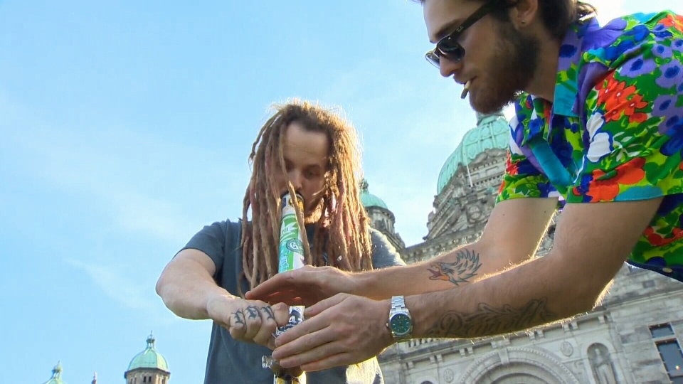 Two people smoke marijuana out of a bong on the lawn of the B.C. legislature in Victoria to mark the first day of legalization. Oct. 17, 2018. (CTV Vancouver Island)
