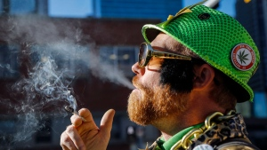 Cannabis user Scott Wells smokes a joint at a rally outside governments offices following the legalization of cannabis in Calgary, Alta., Wednesday, Oct. 17, 2018.THE CANADIAN PRESS/Jeff McIntosh