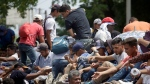 Honduran migrants who are traveling to the United States as a group, get a free ride in the back of a trailer truck flatbed, as they make their way through Teculutan, Guatemala, Wednesday, Oct. 17, 2018. (AP Photo/Moises Castillo)
