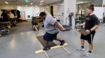 In this Oct. 8, 2018, photo, former NFL football player Vaughn Parker, left, balances himself on a plank of wood as he works with Cole Tomlinson during a range of motion and balance evaluation at Exos in Carlsbad, Calif. Parker played for the San Diego Chargers and Washington Redskins during his time in the NFL. (AP Photo/Gregory Bull)