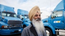 Nachhattar Chohan, president of CH Expedite stands amongst a few of his trucks in Mississauga, Ont., Tuesday, Oct. 16, 2018. THE CANADIAN PRESS/Cole Burston