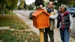 In this Oct. 22, 2013 photo, Little Free Library creator Todd Bol, left, and Eddye Watkins, whose yard the library was erected in, place decorative pieces atop the Amish made, wooden library in Minneapolis. (David Joles/Star Tribune via AP)