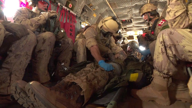 Canadian peacekeepers conduct a medical evacuation simulation aboard a Chinook helicopter in Gao, Mali.