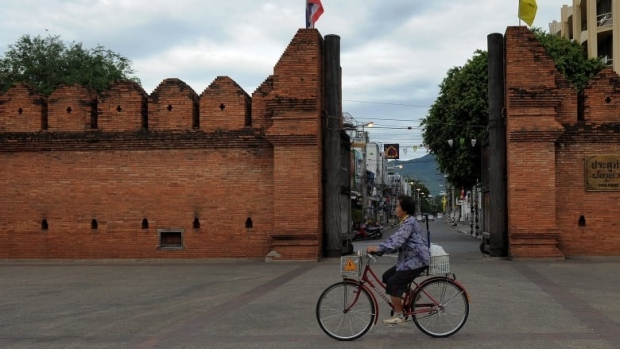 A woman rides her bicycle past the Tha Phae Gate in Chiang Mai, Thailand, in 2010. CCTV video footage allegedly showed a Canadian and a Briton spraypainting a red brick wall near the gate, the main entrance to the city's old town. The pair were arrested and could face jail time or a large fine. (Manan Vatsyayana/AFP)