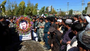 Civilians and military personnel stand beside the grave of Gen. Abdul Raziq, Kandahar police chief, who was killed by a guard, as the pay respect during his burial ceremony in Kandahar, Afghanistan, Friday, Oct. 19, 2018. (AP Photo)