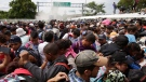 Mexican Federal Police spray tear gas during clashes with thousands of Central American migrants, at the border crossing in Ciudad Hidalgo, Mexico, Friday, Oct. 19, 2018. Central Americans traveling in a mass caravan broke through a Guatemalan border fence and streamed by the thousands toward Mexican territory, defying Mexican authorities' entreaties for an orderly migration and U.S. President Donald Trump's threats of retaliation. (AP Photo/Moises Castillo)