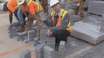 Construction workers and Sean Irvine laying bricks along Dundas Place