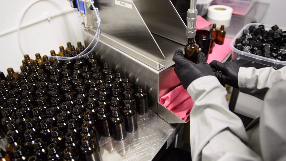 Workers package cannabis oil at Canopy Growth Corporation's Tweed facility in Smiths Falls, Ont., on Monday, Feb. 12, 2018. (THE CANADIAN PRESS/Sean Kilpatrick)