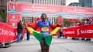 Shure Demise celebrates after crossing the finish line as the first woman at the Scotiabank Toronto Waterfront Marathon in Toronto, Sunday, Oct, 18, 2015. THE CANADIAN PRESS/Marta Iwanek