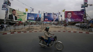 In this Tuesday, Oct. 16, 2018, photo, a man rides his motorbike in front of campaign posters for parliamentary candidates, in Kabul, Afghanistan. (AP Photo/Rahmat Gul)