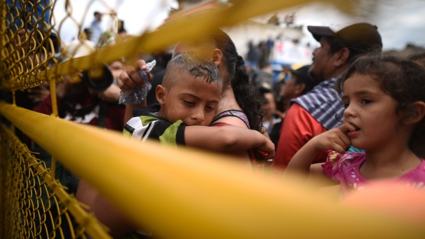 Hundreds of Honduran migrants remain stranded on one of the bridges that crosses the Suchiate River, the natural border between Guatemala and Mexico, in Tecun Uman, Guatemala, 19 October 2018. Thousands of migrants from Honduras pushed their way through the police cordon in Tecun Uman, a border point between Mexico and Guatemala, and crossed into Mexican territory. EPA/EDWIN BERCIAN