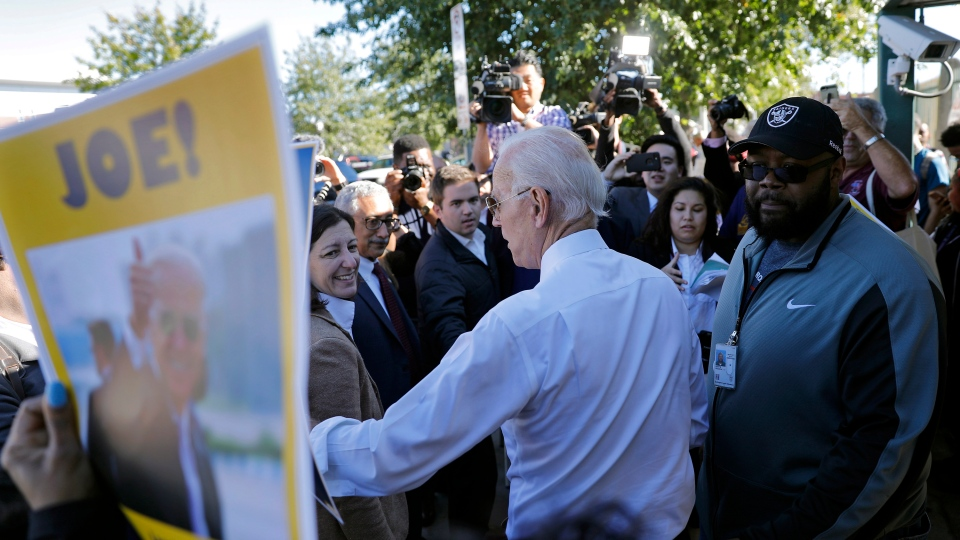 Former Vice President Joe Biden, center, and other local elected officials and candidates greet Newport News Shipyard workers outside the 46th Street gate Friday, Oct. 19, 2018 in Newport News, Va. Union leaders held a lunch celebrating Biden before he greeted Newport News Shipyard workers outside of the 46th Street gate. (Jonathon Gruenke/The Daily Press via AP)