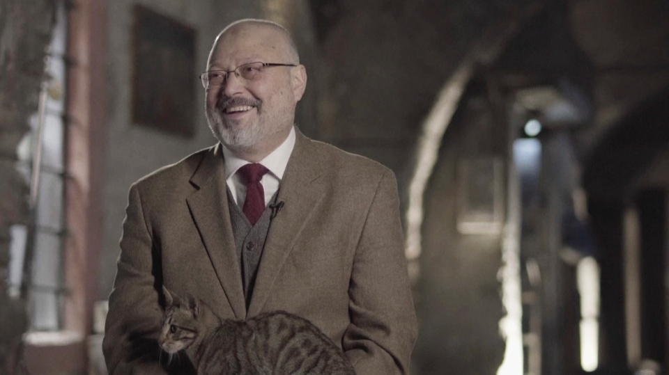 In this image made from a March 2018 video provided by Metafora Production, Jamal Khashoggi reacts as a cat jumped on his lap, while speaking in an interview at an undisclosed location. (Metafora Production via AP)
