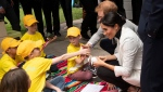 Prince Harry and his wife Meghan, the Duchess of Sussex, talk with school children as they attend a lunchtime reception hosted by Prime Minister Scott Morrison with Invictus Games competitors, their family and friends in the city's central parkland in Sydney on Sunday, Oct. 21, 2018. (Paul Edwards/Pool Photo via AP)