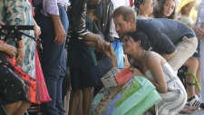 Prince Harry and Meghan, Duchess of Sussex receive gifts from the crowd as they walk along Kingfisher Bay Jetty during a visit to Fraser Island, Australia, on Oct. 22, 2018. (Kirsty Wigglesworth / AP)