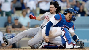 Boston Red Sox's Andrew Benintendi, left, beats the throw to Los Angeles Dodgers catcher Yasmani Grandal, right, to score on a single by Mookie Betts during the sixth inning of a baseball game in Los Angeles, Sunday, Aug. 7, 2016. (AP Photo/Alex Gallardo)