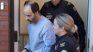 Matthew Vincent Raymond, charged with four counts of first degree murder, is escorted from provincial court in Fredericton on Oct. 22, 2018. (THE CANADIAN PRESS / Andrew Vaughan)