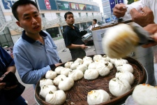 Customers buy steamed buns, called baozi, at a sidewalk stall in Beijing on Thursday, July 12, 2007. (AP / Greg Baker)