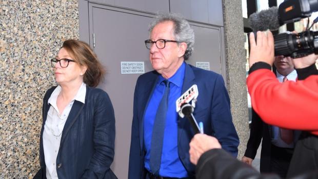 Geoffrey Rush, centre, leaves court