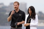 Prince Harry gestures with Meghan, Duchess of Sussex as he operates a remote control car at the Invictus Games driving challenge on Cockatoo Island in Sydney, Australia, Saturday, Oct. 20, 2018. (AP Photo/Kirsty Wigglesworth)