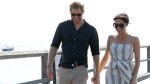 Prince Harry, left, and Meghan, Duchess of Sussex walk along Kingfisher Bay Jetty during a visit to Fraser Island, Australia, Monday, Oct. 22, 2018. (AP Photo/Kirsty Wigglesworth, Pool)
