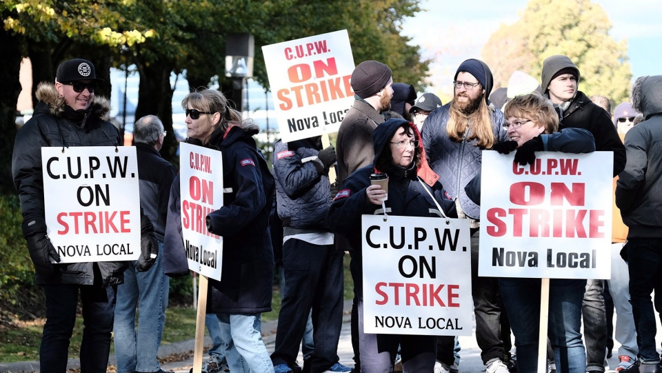 Canadian Union of Postal Workers (CUPW) members stand on picket line along Almon St., in front of the Canada Post regional sorting headquarters in Halifax on Monday, Oct.22, 2018 after a call for a series of rotating 24-hour strikes. (THE CANADIAN PRESS/Ted Pritchard)