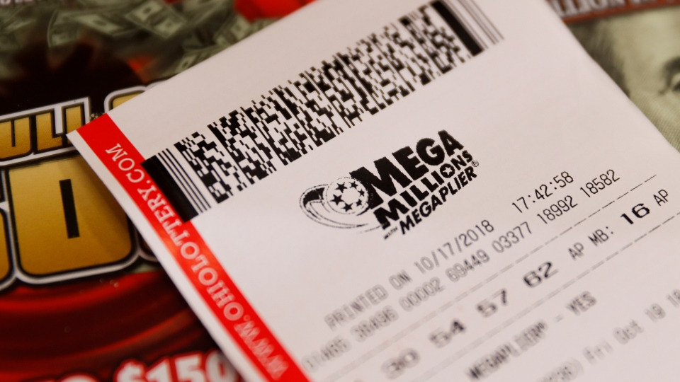A Mega Millions lottery ticket rests on the shop counter at the Street Corner Market, Wednesday, Oct. 17, 2018, in Cincinnati. (AP Photo/John Minchillo)