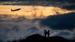 A plane takes off as Andrew Yang, left, and Kevin Jiang take photographs of planes taking off and landing at Vancouver International Airport at sunset, in Richmond, B.C., on Sunday, December 31, 2017.THE CANADIAN PRESS/Darryl Dyck