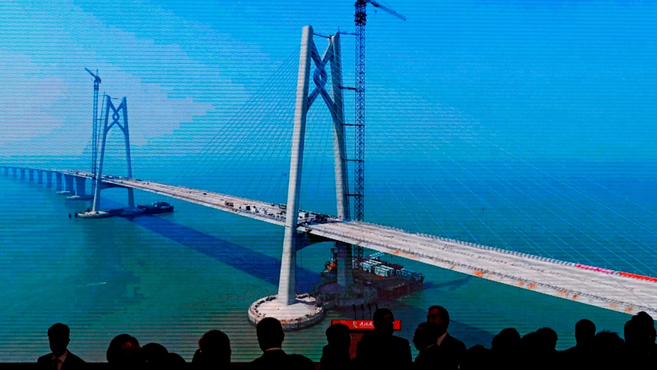 Invited officials are silhouetted on a projector screen showing the construction of the China-Zhuhai-Macau-Hong Kong Bridge ahead of the opening ceremony at the immigration building in Zhuhai in south China's Guangdong province, Tuesday, Oct. 23, 2018. (AP Photo/Andy Wong)