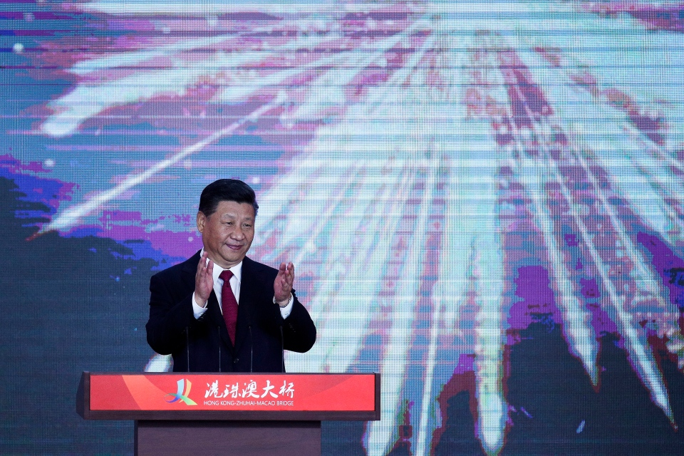 Chinese President Xi Jinping applauds on stage after official opening of the China-Zhuhai-Macau-Hong Kong Bridge, the world's longest cross-sea project, which has a total length of 55 kilometers (34 miles), in Zhuhai in south China's Guangdong province, Tuesday, Oct. 23, 2018. (AP Photo/Andy Wong)