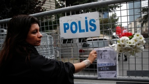 Sahar Zeki, an activist and a friend of slain Saudi writer Jamal Khashoggi, attaches a picture of him and a bouquet of flowers on the barriers blocking the road leading to Saudi Arabia's consulate in Istanbul, Tuesday, Oct. 23, 2018. (/Lefteris Pitarakis/THE ASSOCIATED PRESS)
