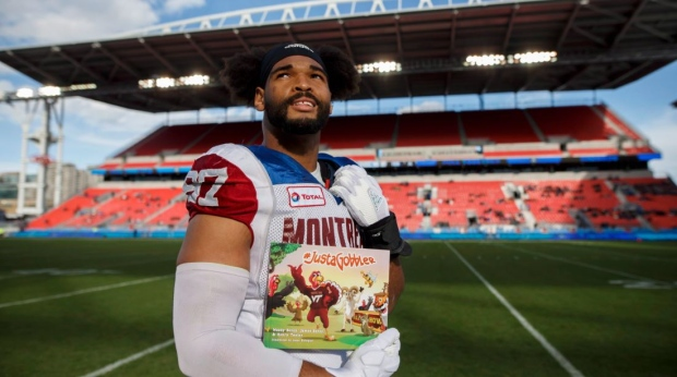 Montreal Alouettes defensive tackle Woody Baron (97) poses with his children's book on the sidelines in Toronto on Saturday, Oct. 20, 2018. Woody Baron finds the spectre of tangling with a hulking offensive lineman much less daunting than sitting before young children. The Montreal Alouettes rookie defensive lineman has co-authored a book entitled #JustaGobbler with his uncle, James Baron, and Henry Taylor. The 38-page hardcover publication was released in August for third- and fourth-graders. THE CANADIAN PRESS/Cole Burston