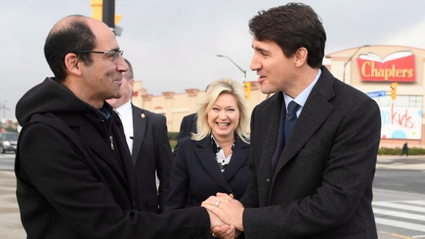 Prime Minister Justin Trudeau talks to a commuter as Mayor Bonnie Crombie looks on at the City Centre transit terminal in Mississauga, Ont., Tuesday, Oct.23, 2018. (Nathan Denette / THE CANADIAN PRESS)