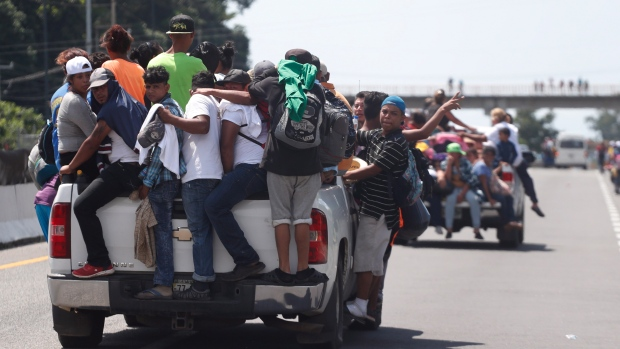 Central American migrants making their way to the U.S. in a large caravan cling to the trucks of drivers who offered them free rides, as they arrive to Tapachula, Mexico, Sunday, Oct. 21, 2018. (AP Photo/Moises Castillo)