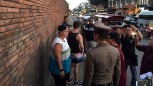 In this Thursday, Oct. 18, 2018, photo, Canadian Brittney Schneider, left, and British Furlong Lee, second left, stand in front of Tha Pae Gate in Chiang Mai province, northern Bangkok, Thailand. They face up to 10 years in prison on charges of spraying paint on an ancient wall in northern Thailand, police said Friday. (Chiang Mai News via AP)