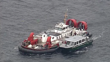 Passengers on a whale watching boat are transferred onto a hovercraft in the Strait of Georgia on Oct. 23, 2018. (CTV/Chopper 9)