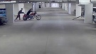 Surveillance camera still of two men walking Adam Martin's Harley Davidson out of his parking spot and into the back of a van on October 17, 2018