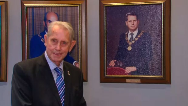 Gordon Krantz stands beside a photograph of his younger self after being re-elected mayor of Milton.