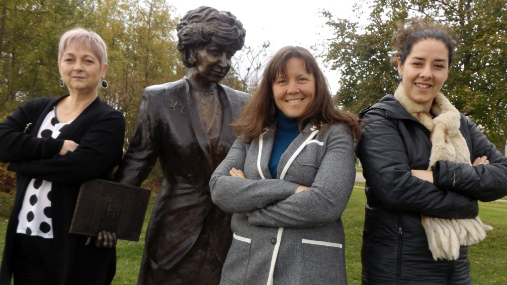 Three councillors pose with Kim Campbell's statue