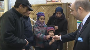 Southwest borough mayor Benoit Dorais hands over house keys to the Marwah family, who are now living in a home built by Habitat for Humanity.