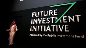 A Saudi participant walks in front of a banner for the Future Investment Initiative conference, in Riyadh, Saudi Arabia, Wednesday, Oct. 24, 2018. (AP Photo/Amr Nabil)