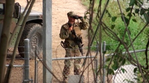 In this April 10, 2018, file frame from video, a National Guardsman watches over Rio Grande River on the border in Roma, Texas. (AP Photo/John Mone, File)