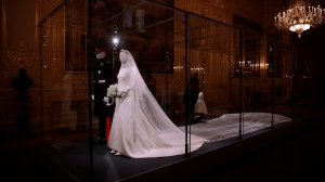 The wedding dress with a five-meter-long veil that Meghan the Duchess of Sussex wore and an identical uniform to the specially commissioned one Prince Harry wore at their May 19, 2018, wedding, are displayed as part of an exhibition entitled 'A Royal Wedding: The Duke and Duchess of Sussex' in the Grand Reception Room at Windsor Castle in Windsor, near London, England, Thursday, Oct. 25, 2018. (AP Photo/Matt Dunham)