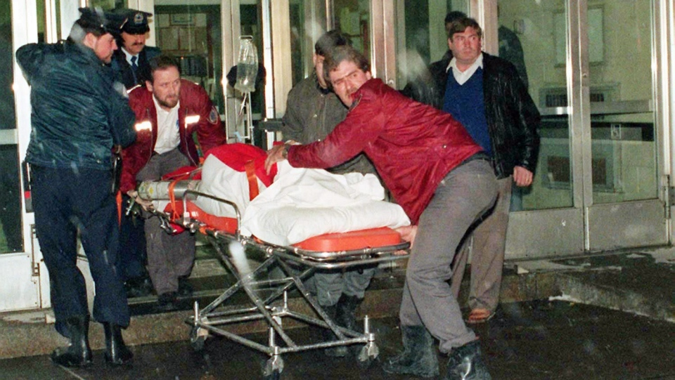 An injured person is wheeled away from the University of Montreal after a gunman, Marc Lepine, opened fire in a packed classroom in Montreal on Dec. 6, 1989. (CP PHOTO - Shaney Komulainen)