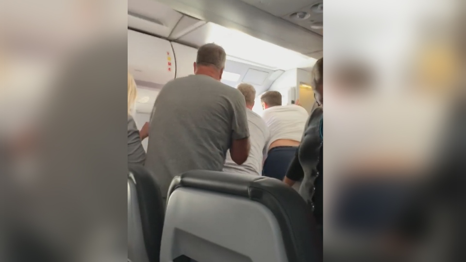 Passengers scrambled to keep a man from falling out of a plane after he reportedly opened a cabin door. (Kathleen Ingham / Facebook)