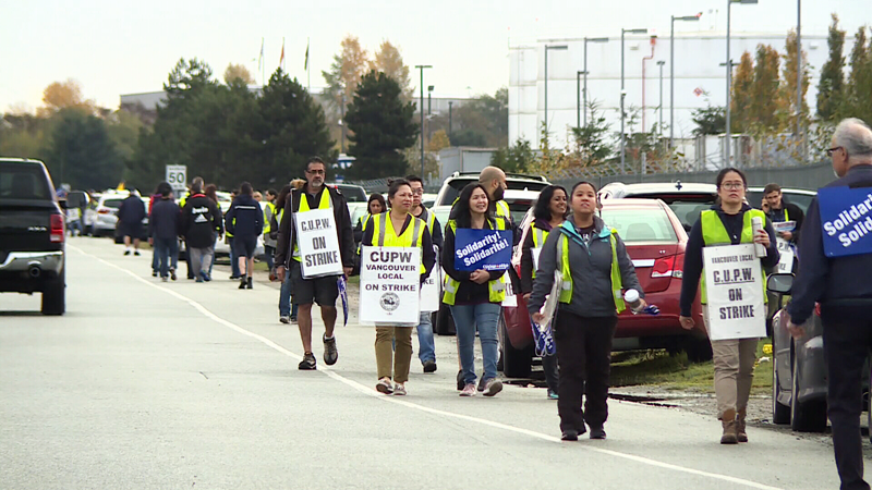 Unionized postal workers strike outside a Canada Post facility in Richmond, B.C. on Friday, Oct. 26, 2018.