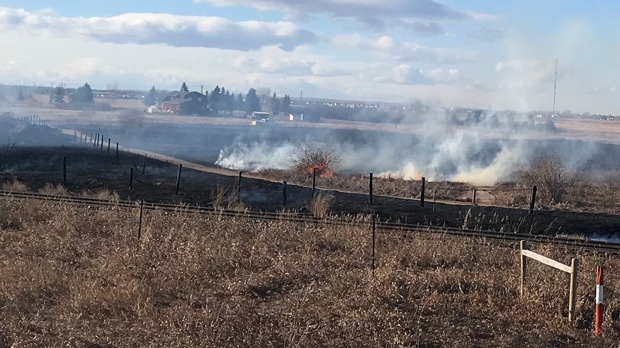 Flames, smoke and charred ground on a rural property east of Calgary
