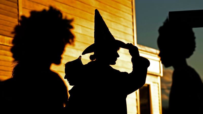Parents dressed as Wizard of Oz characters, from left, the Lion, the Tin Man and the Wicked Witch, wait their children trick-or-treat at a shopping center at sunset in Freeport, Maine, Tuesday, Oct. 31, 2017. (AP Photo/Robert F. Bukaty)