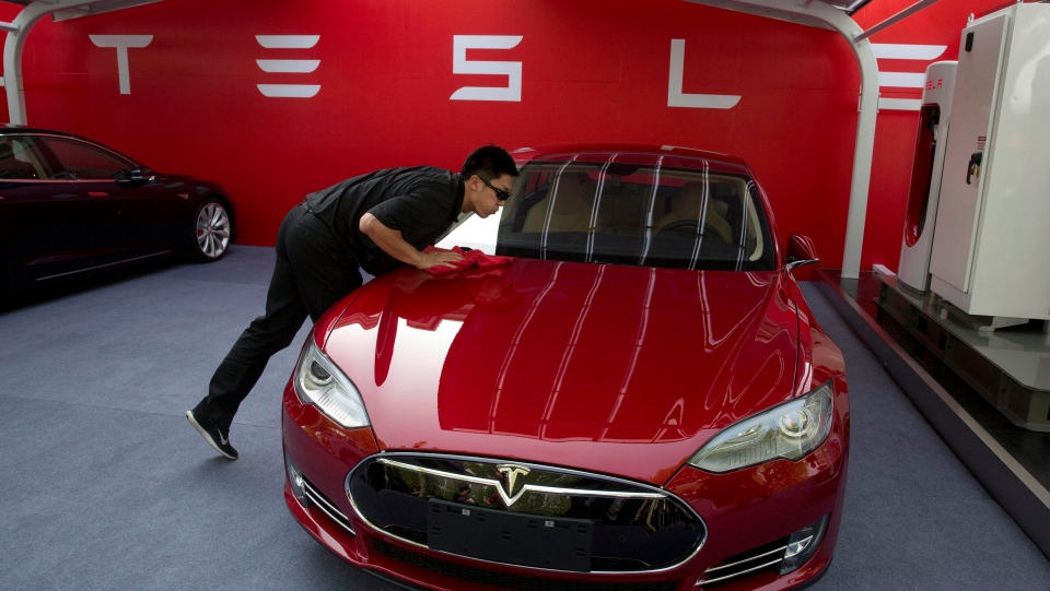 In this April 22, 2014, file photo, a worker cleans a Tesla Model S sedan before an event to deliver the first set of cars to customers in Beijing. (AP Photo/Ng Han Guan, File)