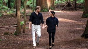 Prince Harry and Meghan, Duchess of Sussex walk through a Redwoods forest in Rotorua, New Zealand, Wednesday, Oct. 31, 2018. (AP Photo/Kirsty Wigglesworth,Pool)